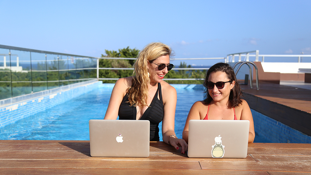 Remote workers on laptops at rooftop pool in Playa del Carmen, Mexico